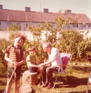 Me (centre) with my younger brother and father, fixing new ropes to the garden swing, an annual event (c. 1975)